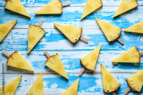 Pineapples on ice cream sticks on wooden background. Minimal summer concept. - 206901179