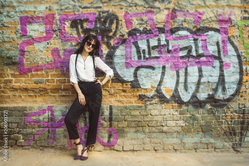 Stylish young woman on graffiti background. Portrait of a fashionable female in sunglasses. - 206903721