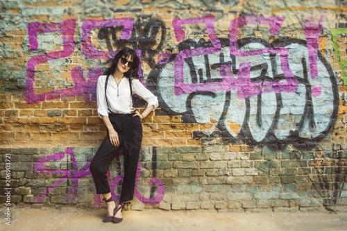 Fotobehang Graffiti Stylish young woman on graffiti background. Portrait of a fashionable female in sunglasses.