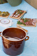 Homemade lard in clay pots, sausage and brined pickles set up on a table at a rustic garden party