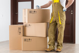 Worker standing near delivered boxes in apartment. Delivery background. - 206908143
