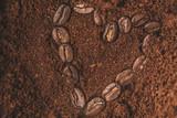 A coffee bean heart in ground coffee
