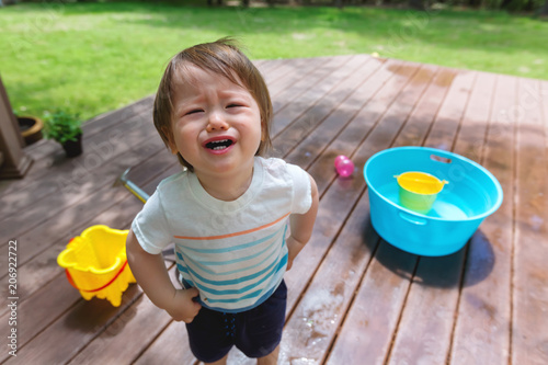 Upset crying toddler boy playing with water outside