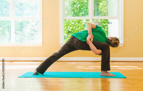 Wall mural Man in a yoga pose inside a big bright room