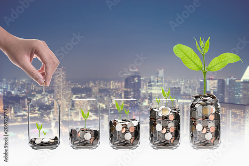 Hand putting mix coins and seed in clear bottle on cityscape photo blurred cityscape background,Business investment growth concept - 206927770