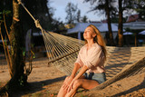 Young european barefoot girl resting on sand in white wicker hammock. Concept of tropic resort and vacations on islands. - 206934767