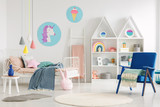 Colorful kid's bedroom interior with a unicorn and ice cream poster, bed with sheets, rabbit pillow, shelves and blue armchair with a blanket