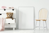 Poster with mockup between chair and cabinet with teddy bear in kid's room interior. Real photo - 206946750