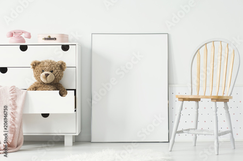 Leinwanddruck Bild Poster with mockup between chair and cabinet with teddy bear in kid's room interior. Real photo