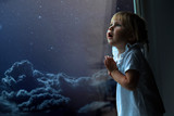 the child looks out the window into the night sky - 206959398