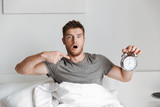 Shocked young man showing alarm clock while sitting in bed - 206971757
