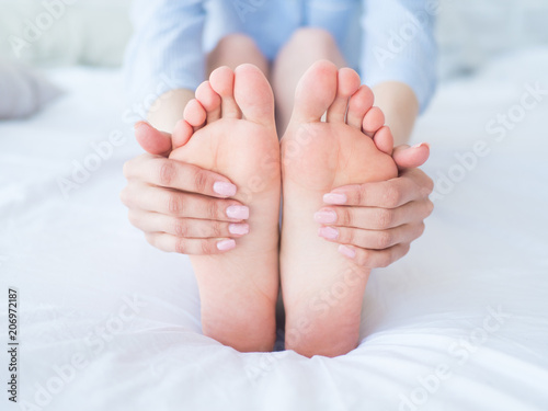 Closeup woman hands doing foot massage. Color picture