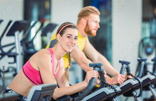 Leinwanddruck Bild Fitness Frau und Mann beim Fahrrad fahren im Fitnessstudio