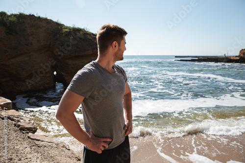 Młody sportowiec siedzi przy seashore