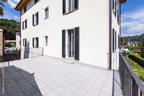 Na zewnątrz nowoczesny biały dom z dużym tarasem