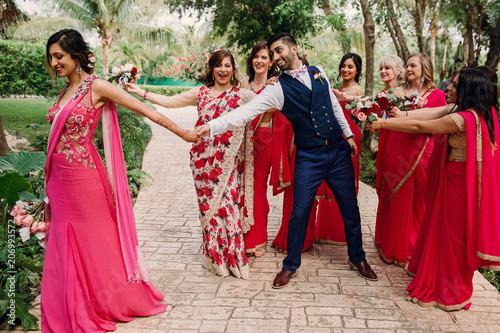 Foto Murales Funny scenes with bridesmaids trying to keep Hindu bride away from groom