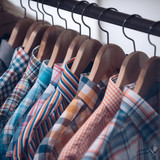Shirts of various colors hang in shop. Shirts on hangers in clothing shop. Clothes rack in menswear store. Fashion and style. Shopping or sale and purchase - 206994361