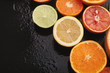 Leinwanddruck Bild - Heap of citruses and juice glass on black background