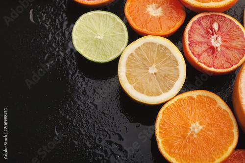 Leinwanddruck Bild Heap of citruses and juice glass on black background
