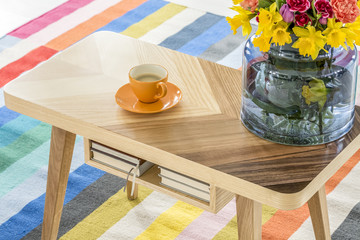 Close-up of a wooden table with a cup of coffee and a bouquet of spring flowers standing on a colorful striped rug