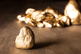 golden nuggets on wooden surface - 207026797