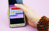 A woman holds a mobile phone with a menstruation calendar - 207030903