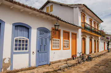 View of cobblestone alley with colorful old houses and bicycles in Paraty, an amazing and historic town totally preserved in the coast of the Rio de Janeiro State, southwestern Brazil © Celli07