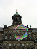 Historic city hall with a colorful soap bubble floating around in the cool air of Amsterdam, Netherlands
