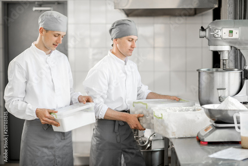 Two male confectioners holding containers with food ingredients standing at the bakery manufacturing