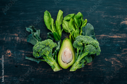 Foto Murales Fresh green vegetables and fruits on a wooden background. Healthy food. Top view. Copy space.