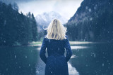 Woman in blue coat standing at lake during snowfall. Selective focus used. - 207044162