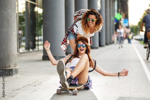 Two female friends playing with skateboard.One girl pushing other from behind.Laughing and fun.