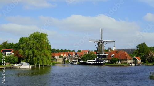 Fotobehang Schip malerische Sicht auf Dorf Sloten am Wasser gelegen mit alten Häusern und Windmühle