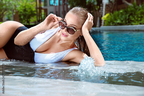 Fotobehang Konrad B. Portrait of a beautiful lady relaxing by the tropical swimming - pool