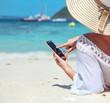 Leinwanddruck Bild - Relaxed lady using a smartphone on a tropical beach