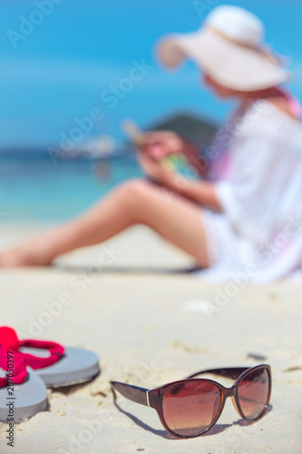 Fotobehang Konrad B. Relaxed lady using a smartphone on a tropical beach