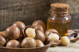 Nuts and macadamia oil on wooden background - Macadamia integrifolia