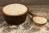 Sesame in a bowl on wooden background with a wooden spoon - 207085384