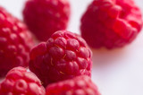 raspberries on a white saucer close up - 207085510