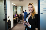Attractive businesswoman using digital tablet in office - 207095340