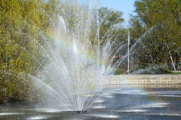 Rainbow in splashes of a fountain as an abstract background