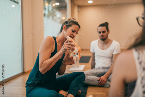 Fotobehang School de yoga Yoga instructor showing anatomy of a knee joint