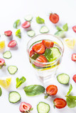 A glass of water with the addition of strawberries, cucumber, mint and lemon. In a circle of bright ingredients on a white background. Detox and Sports Concept