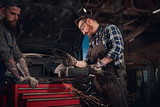 Two bearded auto mechanic in a uniform and safety glasses working with an angle grinder while standing against a broken car in repair garage.  - 207116169