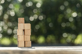 Stacked blank wooden toy blocks on a garden table - 207116983