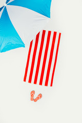 top view of beach umbrella, striped towel and flip flops isolated on white © LIGHTFIELD STUDIOS