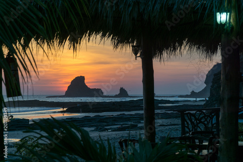 Fotobehang Strand Colorful sunset on the beach in Nicaragua with a rock and banana leafes in the front.