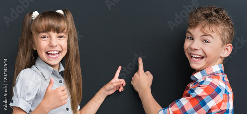 Back to school concept. Portrait of happy young students on dark background. Teenagers smiling and looking at camera. Cute pupil - teen boy and girl at the black chalkboard.