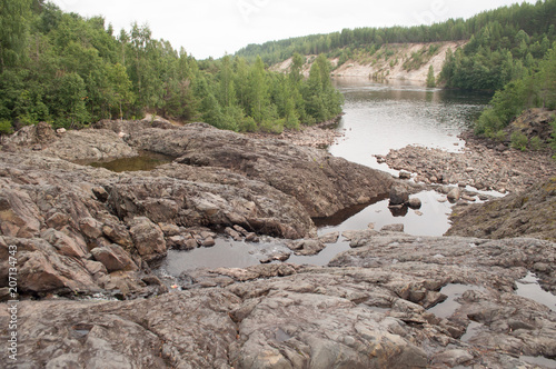 Fotobehang Donkergrijs rocky riverbed and ancient extinct volcano and geyser in Karelia