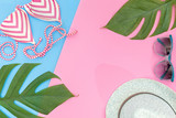 Tropical top view summer holiday concept still life with monstera liana, vine, palm leaves, sunglasses, cream and straw hat on pink background flat lay layout - 207160313